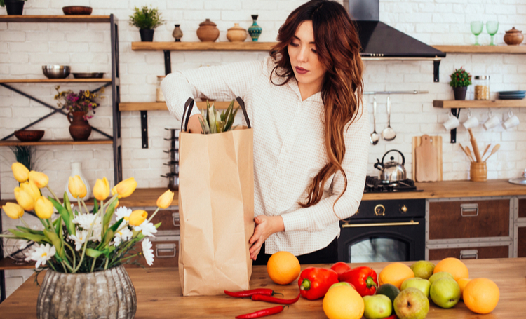 A young woman came back from a supermarket. There are many fruits and vegetables: apples, red peppers, hot peppers, oranges, pears in her bag. She is keeping pineapple in hands. Kitchen at home.
