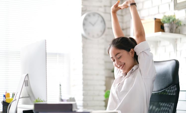Uma mulher se alongando no ambiente de trabalho