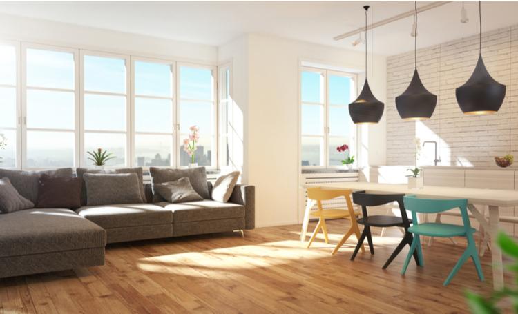 Sala de estar com sofá, cadeiras, pendentes e janelas grandes