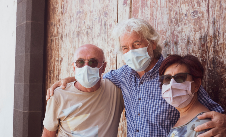 Três adultos seniores lado a lado utlizando máscaras