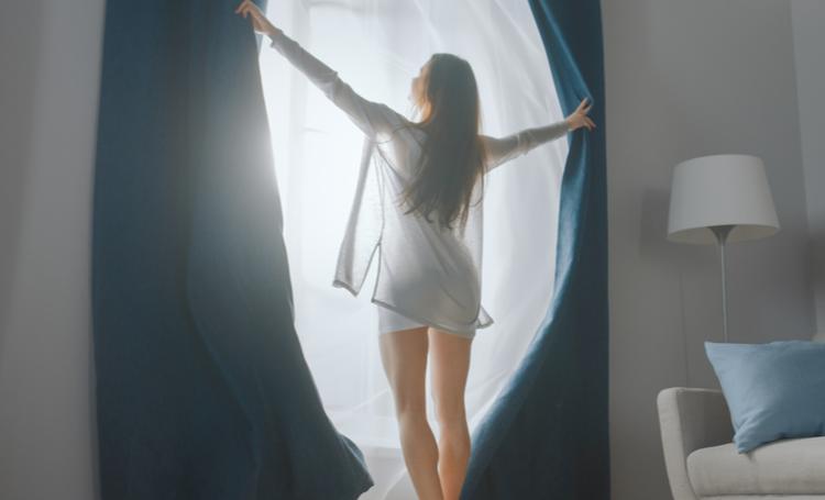Mulher abrindo cortinas de um quarto residencial - LAGUNA