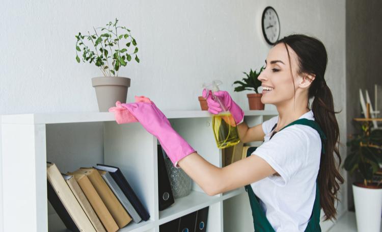 Mulher limpando superfícies para evitar alergias