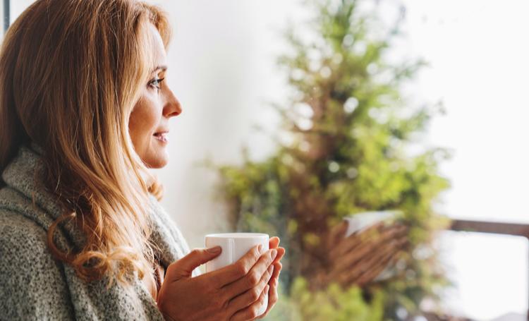 Mulher com xícara na mão aproveitando conforto térmico dentro de residência