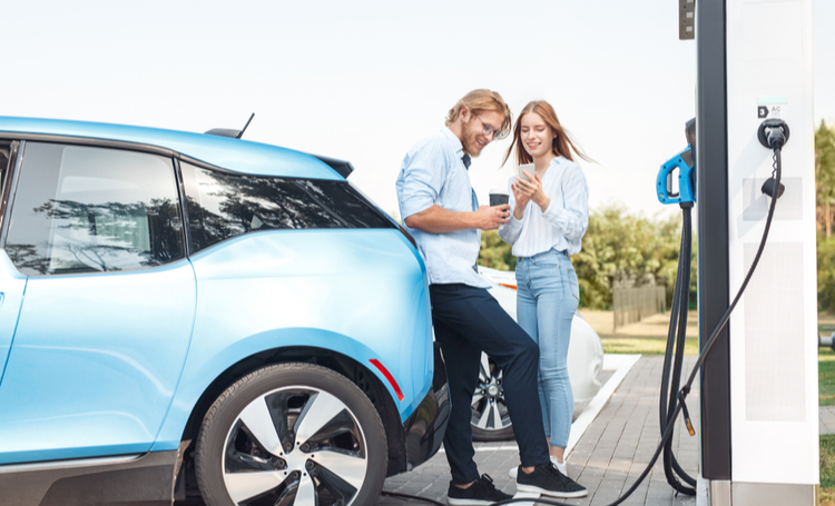 Casal em ponto de recarga para carros elétricos