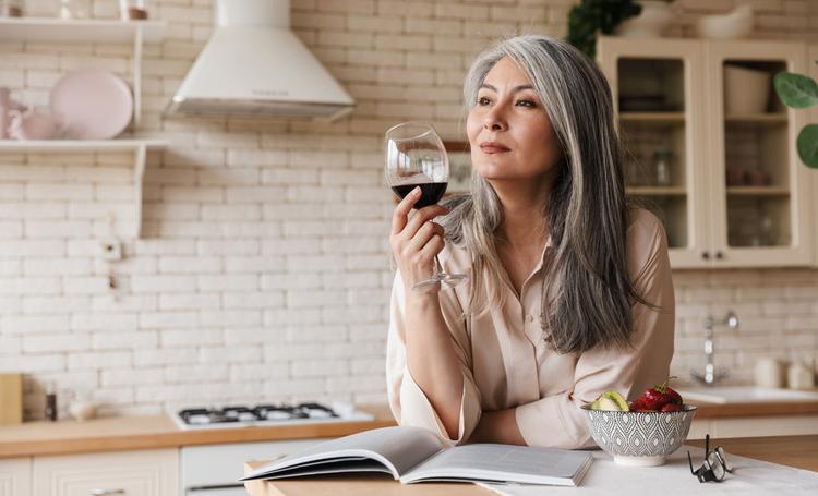 Mulher madura bebendo vinho em sua cozinha